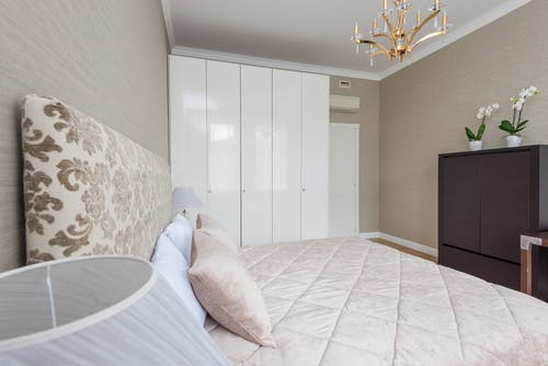 Bed under coverlet with cushions placed near lamp on bedside and closet near door in bedroom with classic chandelier