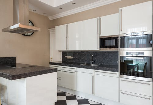 Interior of modern kitchen made in minimalist design with glossy cabinets and built in microwave oven and stove on counter under hood