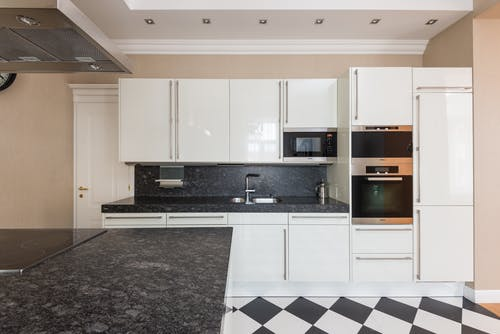Interior design of contemporary kitchen with glossy cupboards and built in stove in marble counter under hood