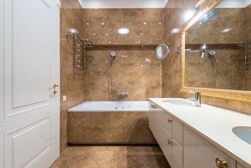 Bathroom interior with bathtub and sinks under mirror