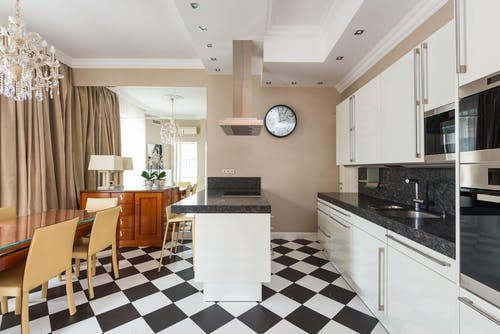 Interior of modern kitchen with marble counter and built in appliances with chairs at wooden dining table in stylish apartment