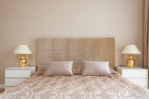 Comfortable bed with pillows and lamps on bedsides