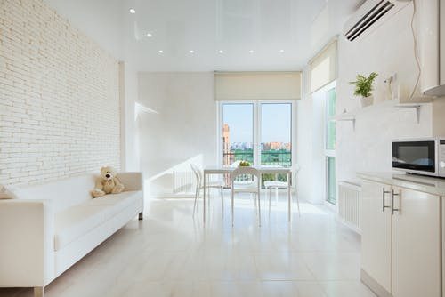 Interior of light kitchen with plush toy on sofa near dining table placed closet to panoramic balcony doors