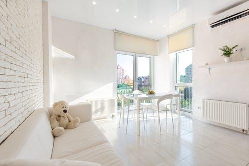 Interior of white kitchen furnished with sofa and chairs and table placed near big windows with blinds