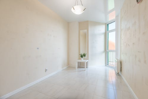 Empty room with tiled floor and potted plant on table near balcony door reflecting on stretch ceiling