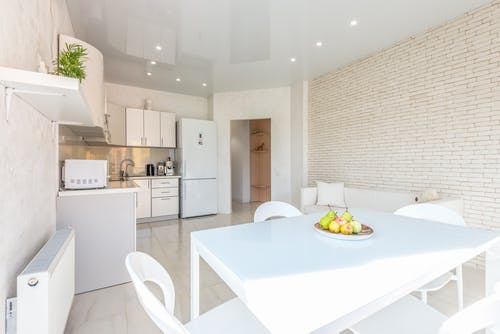 Interior design of spacious light kitchen equipped with built in appliances and dining table with chairs