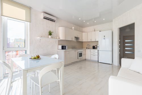 Interior of spacious light kitchen with dining zone