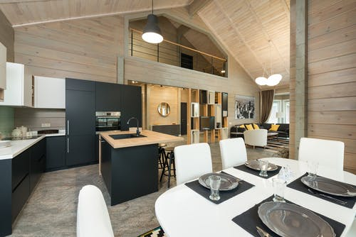 Plates with cutlery and glassware on dining table in stylish kitchen with built in appliances in mansion