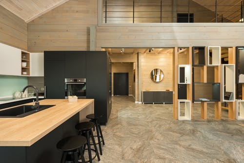 Interior design of modern kitchen with matte cupboards and built in appliances in minimalist spacious private house