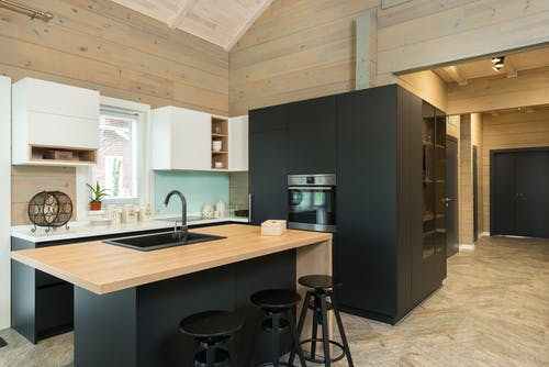 Minimalist style of kitchen with bar chairs at counter and matte cupboards in spacious private house