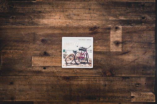 Two Assorted Bicycles Illustration on Brown Wooden Surface