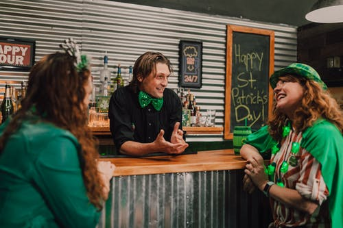 Bartender Talking to Two Women at the Bar Counter During Saint Patrick's Day