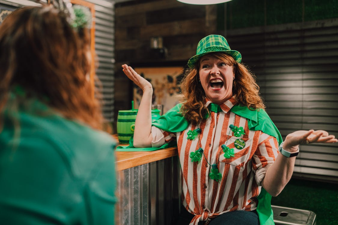 Cheerful adult female with curly red hair yelling and shrugging while chatting with unrecognizable friend in bar during Saint Patricks Day