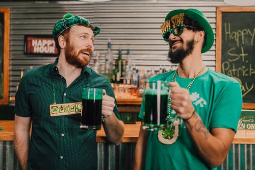 Happy diverse guys drinking beer in bar during Saint Patricks Day