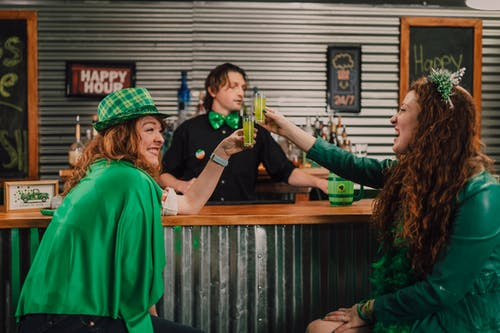 Two Women in Green Clothes Drinking Shots