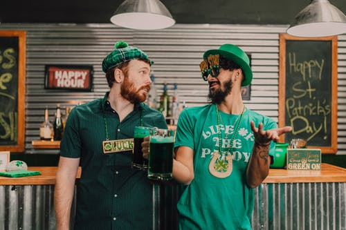 Positive young multiethnic men chatting and drinking beer in pub on Saint Patricks Day