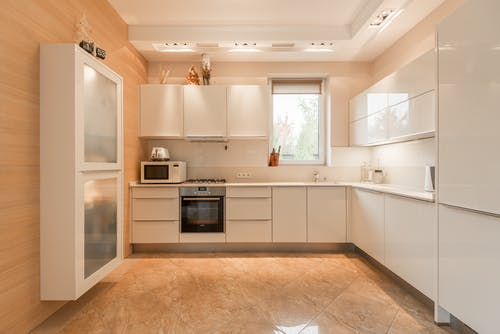 Stylish interior of kitchen with white cupboards and built in oven and stove under lamps on ceiling