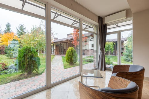 Modern house with comfortable armchairs and panoramic windows with view of green backyard with pathway and bushes