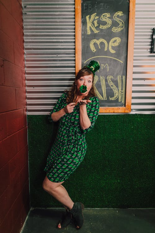 Woman in Green and White Dress Standing Beside Brown Brick Wall