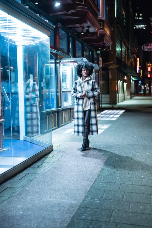 Stylish black woman standing on street in night time
