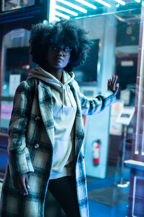 Serious African American woman with curly dark hair in stylish clothes standing near glass wall of building with neon illumination and looking away in evening time