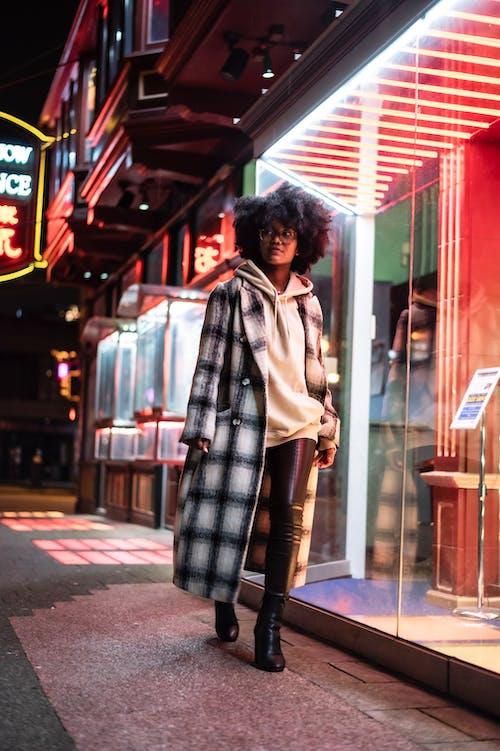 Black woman at night street near illuminated buildings with windows