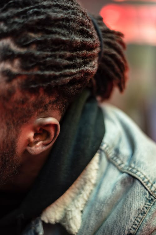 Unrecognizable African American male with beard and black hair sitting on street near glass wall on blurred background in city
