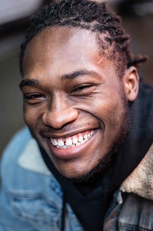 Cheerful African American male with black hair wearing denim jacket looking at camera with toothy smile on street against blurred background