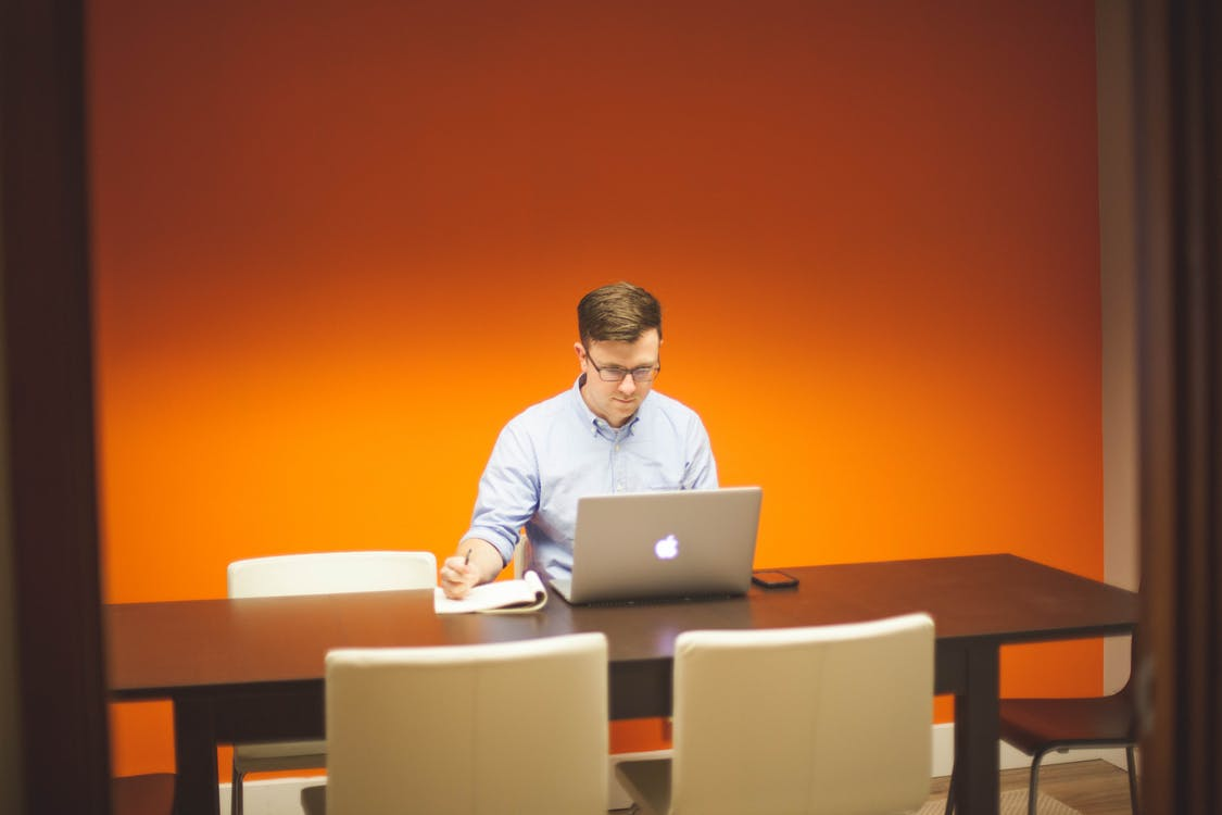 Man Sitting on Chair in Front Table With Silver Macbook