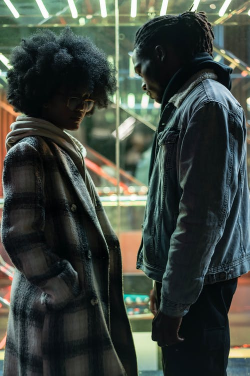 Side view of displease African American couple having misunderstanding and difficulties in relationship standing near glass wall at night