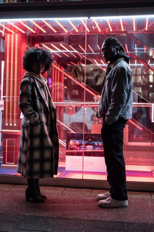 Stylish black couple near transparent building
