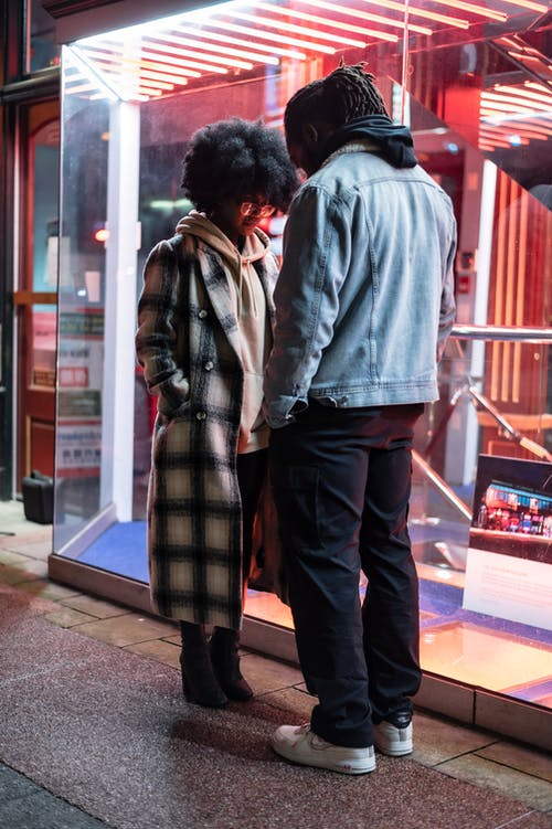 Serious black couple on pathway in evening street