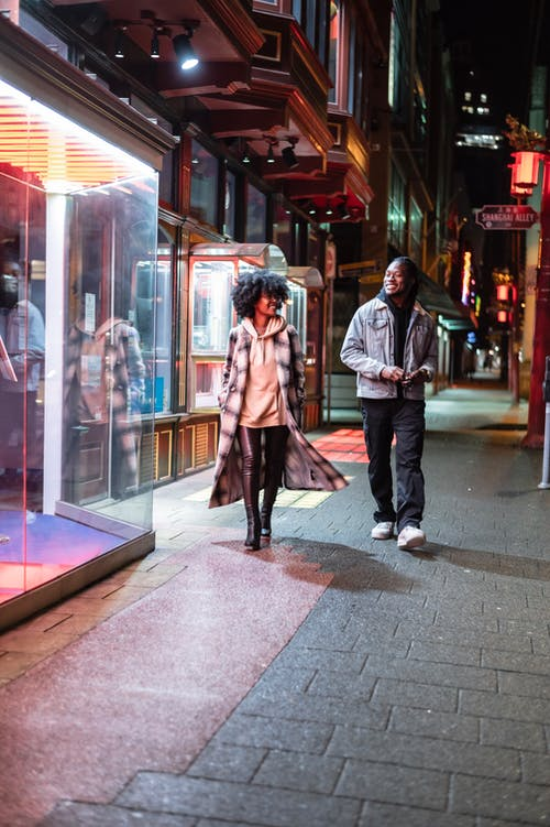 Full body of cheerful African American couple in trendy clothes strolling on paved walkway near glass wall of building in evening time