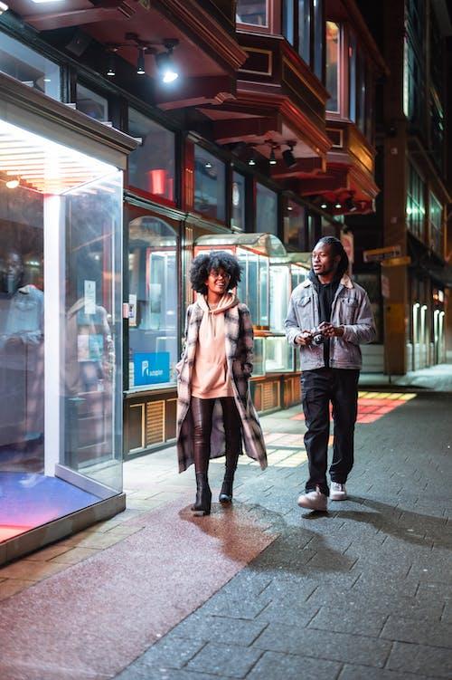 Content black couple walking on evening street