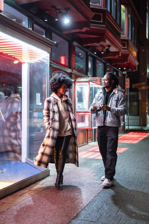 Full body of positive African American male photographer with photo camera strolling on street with black woman in evening time