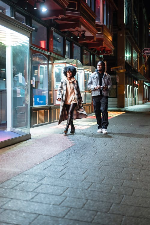 Full body of cheerful African American couple with photo camera strolling on paved walkway near glass walls of modern building in evening time