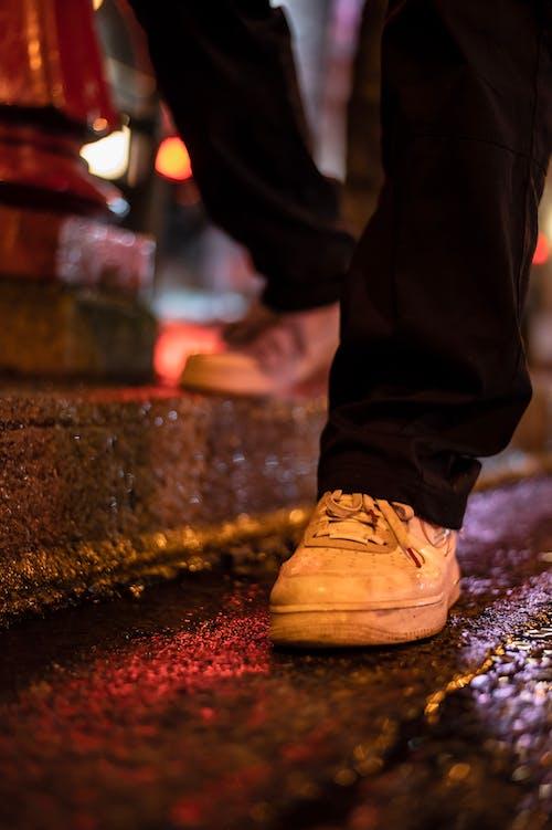 Man in sneakers standing on sidewalk