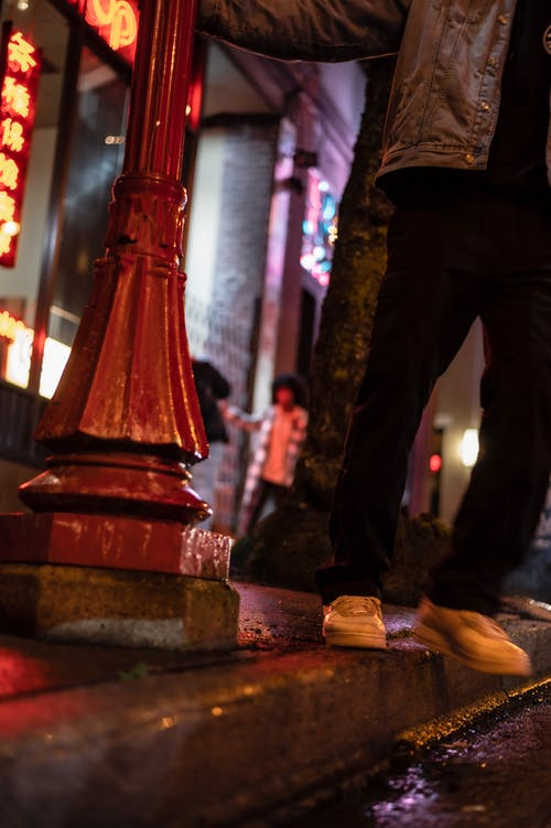 Low angle of unrecognizable male in casual clothes standing on wet sidewalk near post at night