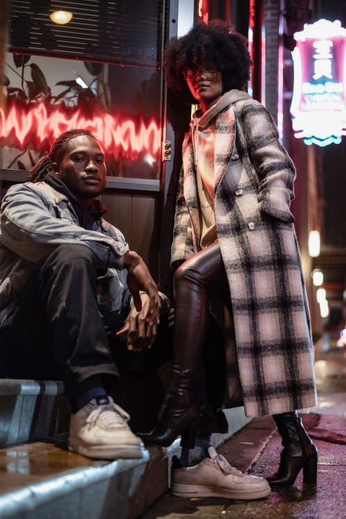 Stylish black friends in outerwear on urban walkway at night
