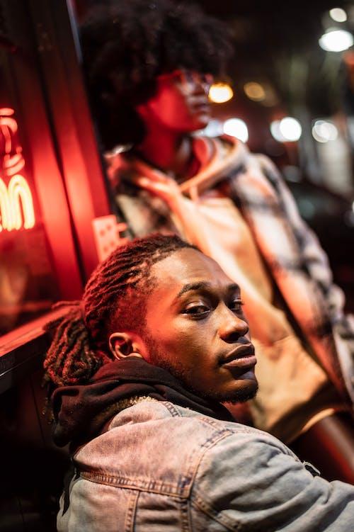 Cool black man against friend in night town