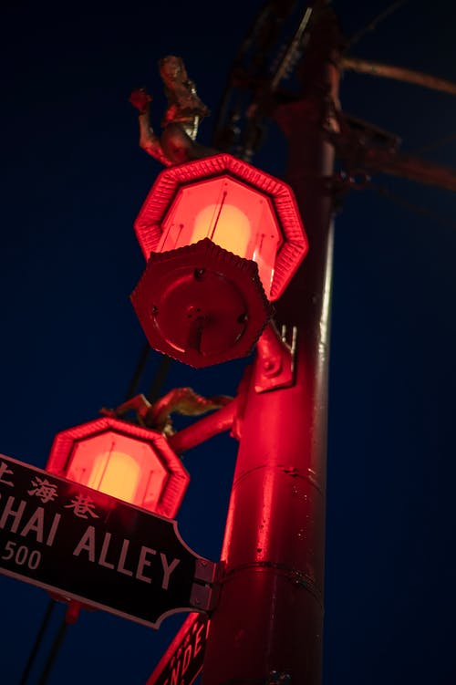 Alley inscription on signboard between neon lanterns in night city