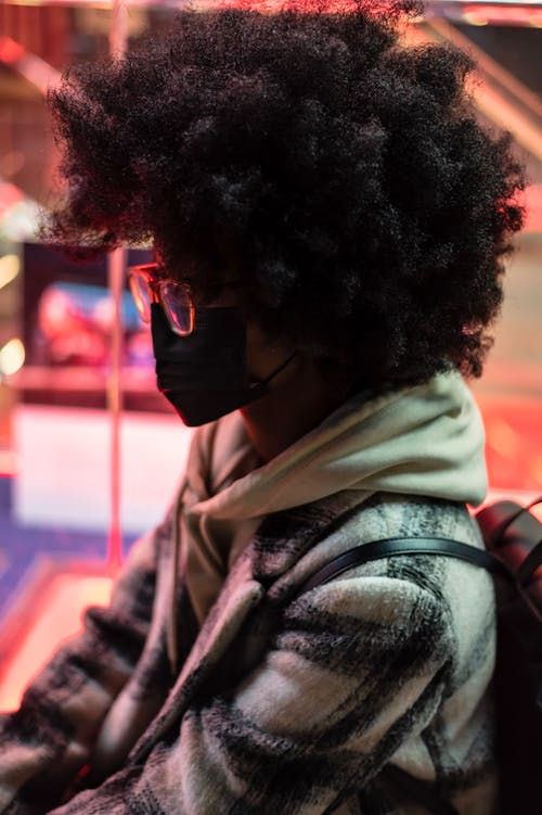 Side view of anonymous ethnic female in cloth face mask and eyeglasses at night on blurred background