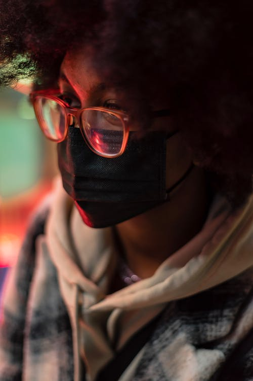 Black woman in textile mask and eyewear in evening