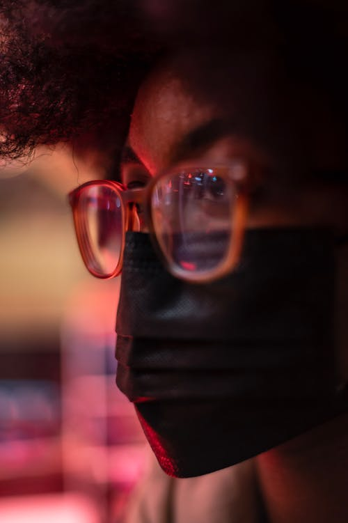 Crop ethnic woman in fabric mask and eyewear at night