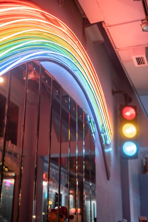 Neon lights with spectrum ornament on building wall at dusk
