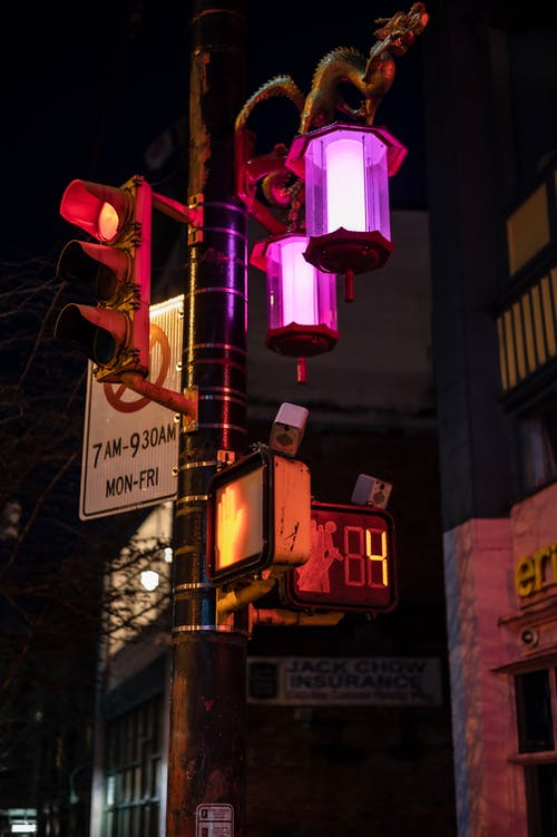 Lanterns on post with restriction sign and numbers with letters against city building at dusk
