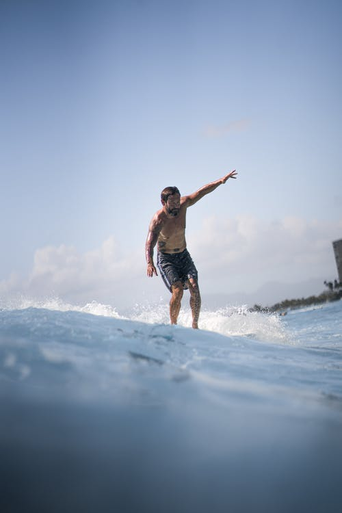 Full body of shirtless male surfer in shorts standing on surfboard in wavy sea against cloudy sky