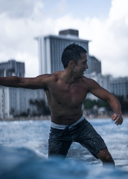 Muscular shirtless male in swimming shorts standing on board in wave of sea against coastal town