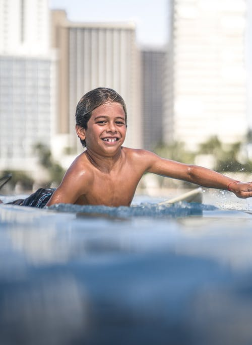 Happy shirtless boy lying on surfboard and swimming in clear sea water against coastal city and looking at camera