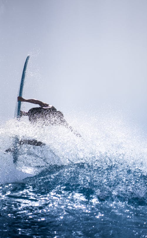 Anonymous strong surfer holding surfboard while flipping over wave in sparkling splashes in sunlight